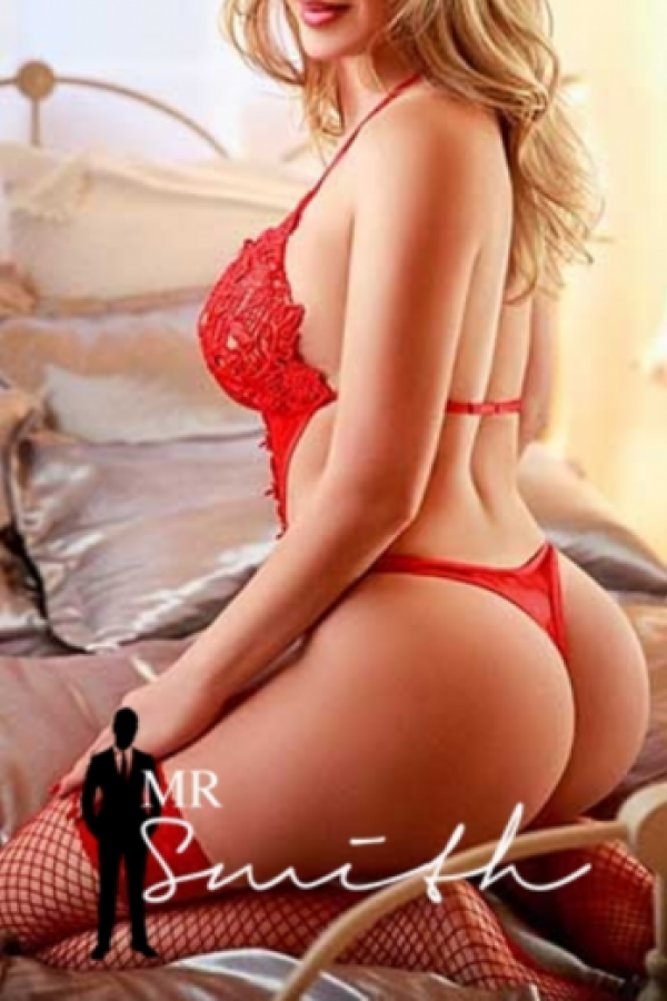 beautiful blonde natalie poses on a bed in her bright red one piece lingerie