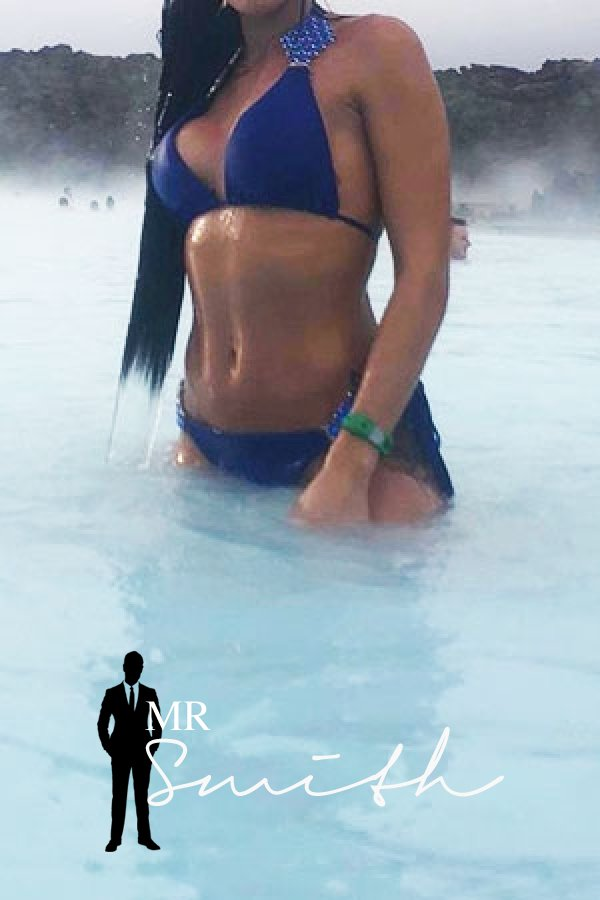 Manchester escort Sahara stands in a pool and shows off her toned body in a blue bikini
