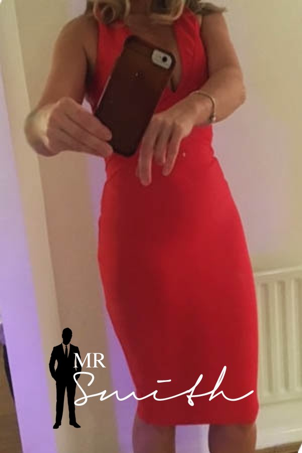 Mature Manchester escort Suzy takes a selfie of herself in a bright red formal dress