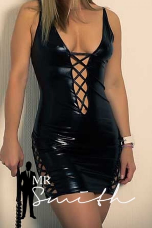 naughty escort natalie is dressed in a leather bdsm dress and holds a whip
