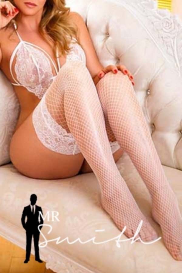 natalie seductively lies on a sofa in a white lingerie set and white stockings