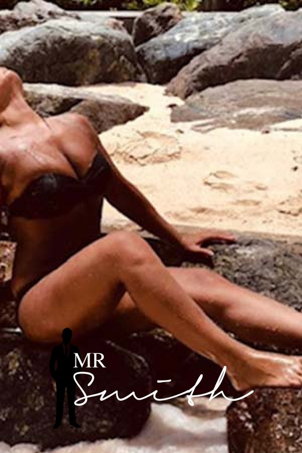 Jenna leans back on a rock on a beach and shows off her sexy tanned body in a black bikini